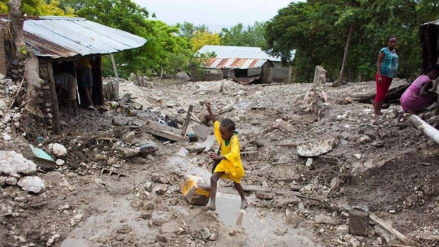 Seven-year-old Redefine Aristile leaps over a puddle in rain-soaked Montrouis, Haiti, Saturday, Aug. 29, 2015. Erika dissipated early Saturday, but it left devastation in its path on the small eastern Caribbean island of Dominica, authorities said. In Haiti, one person died in a mudslide just north of Port-au-Prince. (AP Photo/Dieu Nalio Chery)