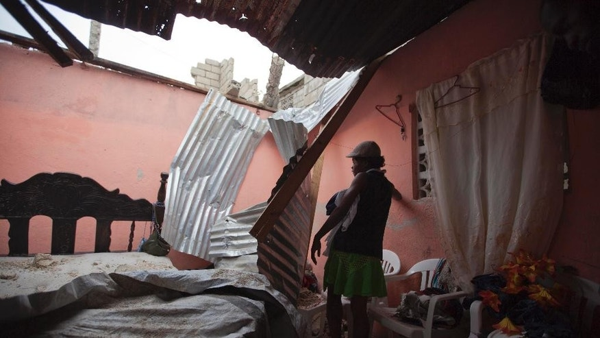 Rose Dormice inspects her bedroom where the roof collapsed during high winds and heavy rains caused by Tropical Storm Erika, in Port-au-Prince, Haiti, Saturday, Aug. 29, 2015. Tropical Storm Erika dissipated early Saturday, but it left devastation in its path on the small eastern Caribbean island of Dominica, authorities said. (AP Photo/Dieu Nalio Chery)