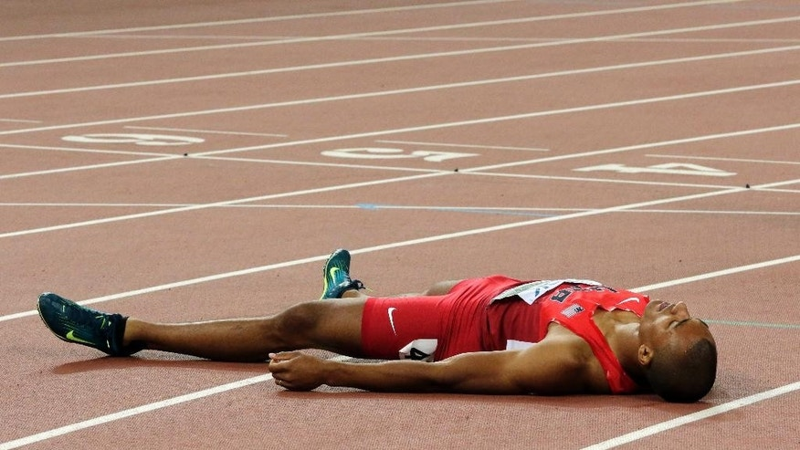 United States' Ashton Eaton lays on the track after crossing the line to win the gold medal  in the decathlon at the World Athletics Championships at the Bird's Nest stadium in Beijing, Saturday, Aug. 29, 2015. (AP Photo/Andy Wong)