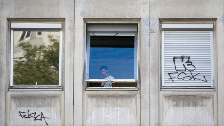 FILE - In this Sunday, Aug. 2, 2015 file photo, a migrant looks out from a window of the Guillaume-Bude secondary school building in Paris, France. With more and more refugees appearing in Europe daily this summer, cities and towns are grappling with a basic but frustrating problem: Where should they all sleep? Tent camps are the most widespread solution for migrants in limbo and refugees seeking asylum, and have cropped up in public squares, meadows and train stations this summer. French humanitarian groups are increasingly converting abandoned public buildings like the school into migrant centers, recognizing that official emergency housing spots created this summer aren't enough to shelter everyone. France has approximately 25,000 beds nationwide designated for asylum seekers but nearly 70,000 applied for asylum last year. (AP Photo/Jacques Brinon, File)