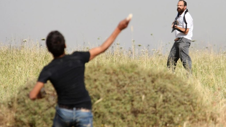 """File - In this May 19, 2012 file photo, a Palestinian throws a stone at an armed Jewish settler during clashes between Palestinians and Jewish settlers in the West Bank village of Assira al-Kibliya. A firebombing last month on a West Bank home, killed an 18-month-old toddler, Ali Dawabsheh, and his father, Saed, and critically wounded his mother and 4-year-old brother. In the wake of the attack, Israeli Prime Minister Benjamin Netanyahu pledged """"zero tolerance"""" for what he called Jewish terrorism. (AP Photo/Nasser Ishtayeh, File)"""