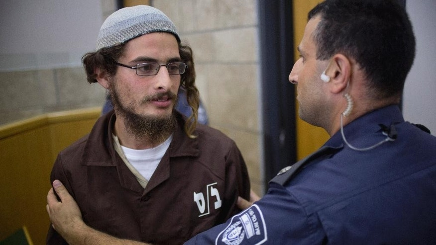 """FILE - In this Tuesday, Aug. 4, 2015 file photo, head of a Jewish extremist group Meir Ettinger appears in court in Nazareth Illit, Israel. A firebombing last month on a West Bank home, killed an 18-month-old toddler, Ali Dawabsheh, and his father, Saed, and critically wounded his mother and 4-year-old brother. In the wake of the attack, Israeli Prime Minister Benjamin Netanyahu pledged """"zero tolerance"""" for what he called Jewish terrorism. (AP Photo/Ariel Schalit, File)"""
