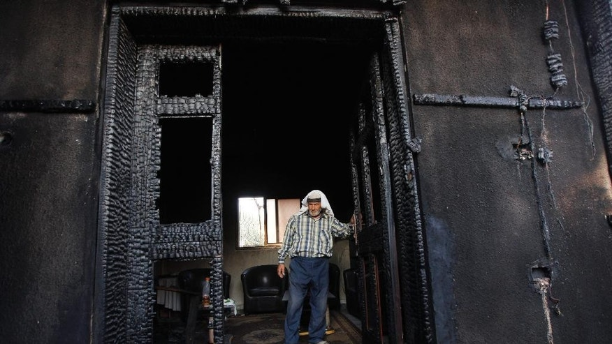 """FILE - In this July 31, 2015 file photo, a Palestinian inspects a house after it was torched in a suspected attack by Jewish settlers, killing an 18-month-old Palestinian child, according to a Palestinian official from the area, at Duma village near the West Bank city of Nablus. In the wake of the attack, Israeli Prime Minister Benjamin Netanyahu pledged """"zero tolerance"""" for what he called Jewish terrorism. (AP Photo/Majdi Mohammed, File)"""