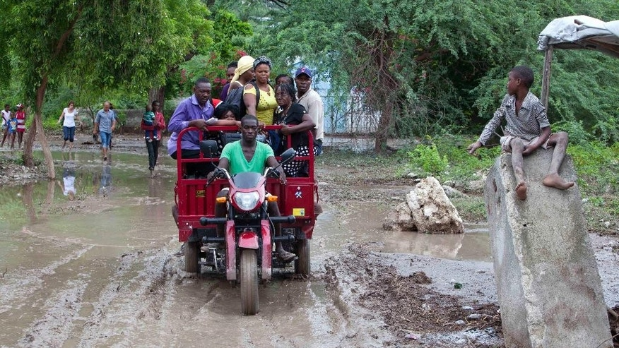 Commuters on their way to the capital are taxied to a bus, after they were temporarily stranded in Montrouis, Haiti, Saturday, Aug. 29, 2015, the site of a mudslide triggered by Tropical Storm Erika. The deadly storm dissipated early Saturday, but it left devastation in its path on the small eastern Caribbean island of Dominica, and parts of Haiti, authorities said. (AP Photo/Dieu Nalio Chery)