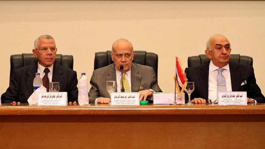 Ayman Abbas, center, head of the Supreme Election Committee, announces the dates for Egypt's parliamentary elections at a news conference in Cairo, Egypt, Sunday, Aug. 30, 2015. The committee announced that long-awaited parliamentary elections will take place in two stages in October and November. Egypt has been without a legislature for three years. In its absence, President Abdel-Fattah el-Sissi holds legislative authority. (AP Photo/Ahmed Gamil)