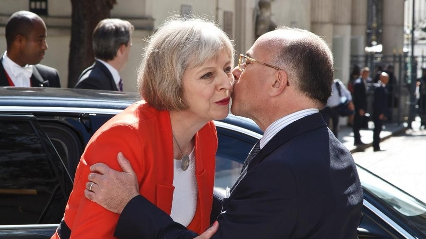British Home Secretary Theresa May, left, is welcomed by French Interior Minister Bernard Cazeneuve, right, for an emergency meeting in Paris, France, Saturday, Aug. 29, 2015. European security and transport chiefs are holding an emergency meeting Saturday in Paris to reconsider train security after American passengers thwarted an Islamic extremist attack on a trip from Amsterdam to Paris. (AP Photo/Michel Euler)