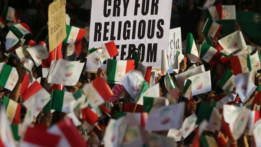 Members of the religious sect Iglesia Ni Cristo (Church of Christ) holds a slogan as they wave their flags during a protest against the Justice Department on Sunday, Aug. 30, 2015 in suburban Mandaluyong city, east of Manila, Philippines. The sect members, who have been doing street protests for four days, has expressed dismay over efforts by Justice Secretary Leila De Lima's department to investigate a criminal complaint filed by an expelled sect minister against the religious group's top leaders. (AP Photo/Aaron Favila)
