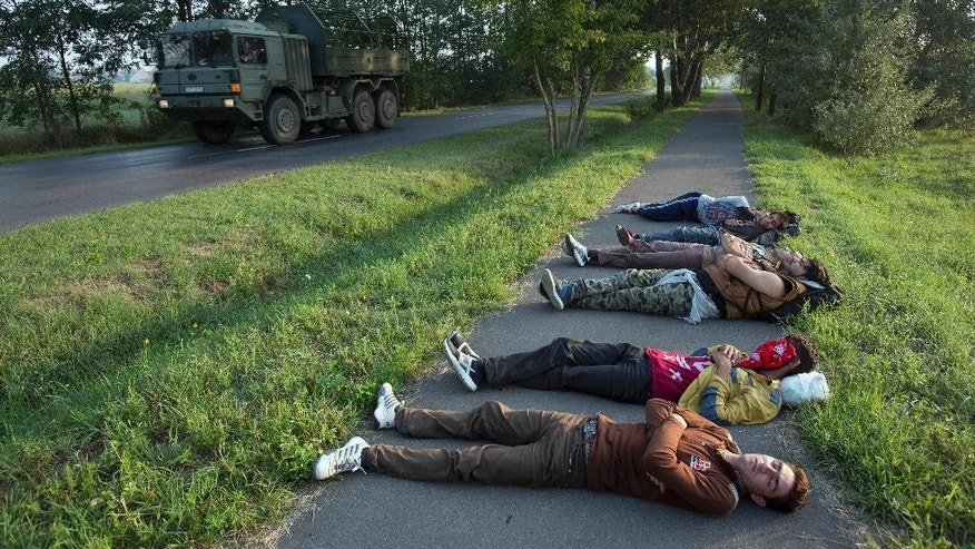 A Hungarian Army truck drives past a group of Afghan men who crossed from nearby Serbia and sleeping on a bicycle path in Morahalom, Hungary, Sunday, Aug. 30, 2015. Migrants fearful of death at sea in overcrowded and flimsy boats have increasingly turned to using a land route to Europe through the Western Balkans. (AP Photo/Darko Bandic)