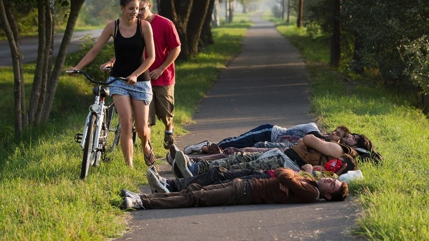 Local cyclists move past a group of Afghan men who crossed from nearby Serbia and sleeping on a bicycle path in Morahalom, Hungary, Sunday, Aug. 30, 2015. Migrants fearful of death at sea in overcrowded and flimsy boats have increasingly turned to using a land route to Europe through the Western Balkans. (AP Photo/Darko Bandic)
