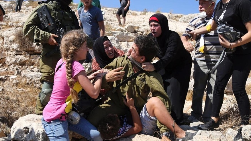 "In this Friday, Aug, 28, 2015 photo, Palestinian women and youth scuffle with an Israeli soldier trying to arrest a 12-year-old boy during a protest near the West Bank village of Nebi Saleh. A video showing the incident has been viewed more than 2 million times on Facebook, and shined a light on Israeli military policies in the territory. The Israeli military said Sunday that a ""violent riot"" broke out at the protest and that it tried to detain the boy because he was hurling rocks. The video sparked accusations from critics that Israel is too heavy-handed in its confrontations with Palestinian protesters, especially minors. (AP Photo)"