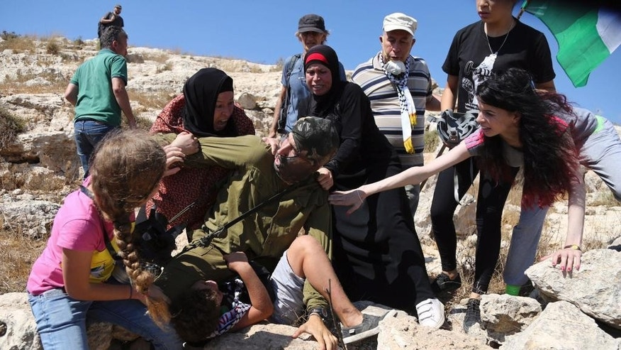 "In this Friday, Aug, 28, 2015 photo, Palestinian women and girls scuffle with an Israeli soldier trying to arrest a 12-year-old boy during a protest near the West Bank village of Nebi Saleh. A video showing the incident has been viewed more than 2 million times on Facebook, and shined a light on Israeli military policies in the territory. The Israeli military said Sunday that a ""violent riot"" broke out at the protest and that it tried to detain the boy because he was hurling rocks. The video sparked accusations from critics that Israel is too heavy-handed in its confrontations with Palestinian protesters, especially minors. (AP Photo)"