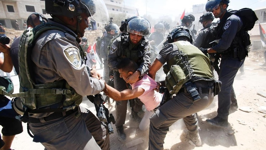 Israeli border police detain a Palestinian during a protest against the Israeli separation barrier, in Beit Jala, West Bank, Sunday, Aug. 30, 2015. (AP Photo/Nasser Shiyoukhi)