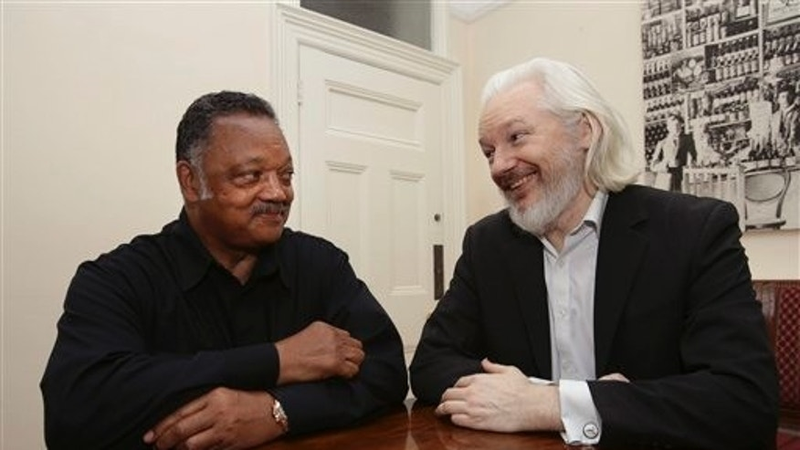 WikiLeaks founder Julian Assange, right, sits with the Rev. Jesse Jackson inside the Embassy of Ecuador in London, Friday Aug. 21, 2015. (The Associated Press)
