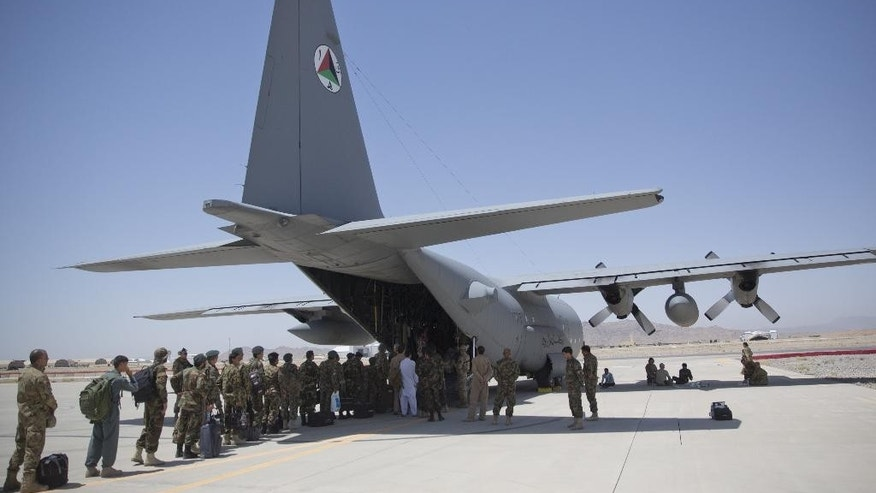 In this Tuesday, Aug. 18, 2015 photo, Afghan National Army soldiers line up to get into a C-130 Hercules, at Kandahar Air Base, in Kandahar, Afghanistan. A series of airports, built by NATO to fight the Taliban, are being handed over to the Afghan government in a civil aviation upgrade that optimists hope will fuel not only regional trade but even tourism. The eight airfields, worth an estimated $2 billion, are scattered around a landlocked and mountainous land whose lack of rail transport or decent roads makes almost every intercity journey a perilous adventure -- even without factoring in attacks from Taliban militants. (AP Photo/Massoud Hossaini)