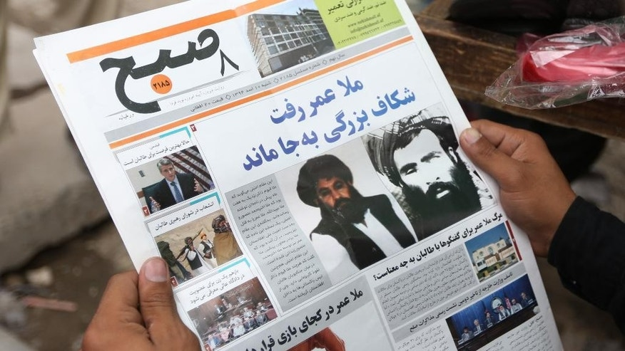 FILE - In this Saturday, Aug. 1, 2015 file photo, an Afghan man reads a local newspaper with photos of the new leader of the Afghan Taliban, Mullah Akhtar Mansoor, center, and former leader Mullah Mohammad Omar who was declared dead, in Kabul, Afghanistan. Defying the fury of Afghanistan's government and warnings from Washington, Pakistani authorities appear to be turning a blind eye to a meeting of hundreds of Taliban followers in Quetta, Pakistan, near the Afghan border, aimed at resolving a dispute over the group's leadership following the death of one-eyed figurehead Mullah Mohammad Omar. (AP Photo/Rahmat Gul, File)