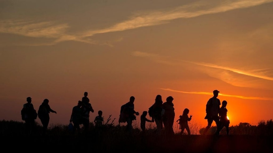 Refugees from the Middle East are silhouetted against the setting sun as they walk on railway tracks from Serbia, in Roszke, Hungary, Sunday, Aug. 30, 2015. Migrants fearful of death at sea in overcrowded and flimsy boats have increasingly turned to using a land route to Europe through the Western Balkans. (AP Photo/Darko Bandic)