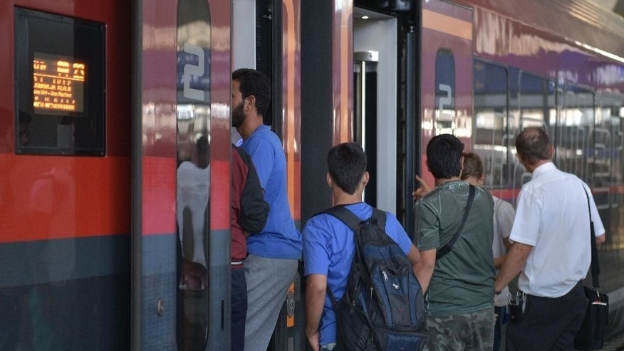 People board a train at the central rail station in Vienna, Austria, on Monday, Aug. 31, 2015. Some hundreds of migrants arrive by train from southern Europe, after making a perilous journeys into Europe. (AP Photo/Hans Punz)