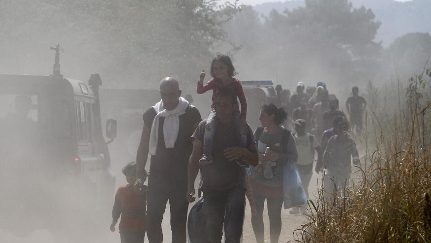 A group of migrants walk along a dusty road towards a transit center for migrants, after crossing the border from Greece to Macedonia, near the southern Macedonian town of Gevgelija, Monday, Aug. 31, 2015. Thousands of migrants have poured into Macedonia to board trains and busses that are taking them a step closer to the European Union's Schengen Area. (AP Photo/Boris Grdanoski)