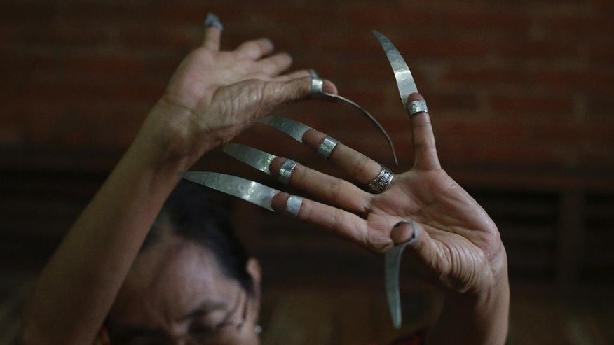 """In this Aug. 2, 2015 photo, Ramon Magsaysay awardee, Filipino Ligaya Fernando Amilbangsa, performs a gesture with a """"Janggay"""" or metal claws on her hand as part of the ethnic dance style called Pangalay at her home in Antipolo, east of Manila, Philippines. Amilbangsa received the Ramon Magsaysay award, regarded as Asia's equivalent of the Nobel Prize, for """"her single-minded crusade in preserving the endangered artistic heritage of southern Philippines,"""" specifically her lifelong work to conserve and promote the ethnic dance style called Pangalay. (AP Photo/Aaron Favila)"""