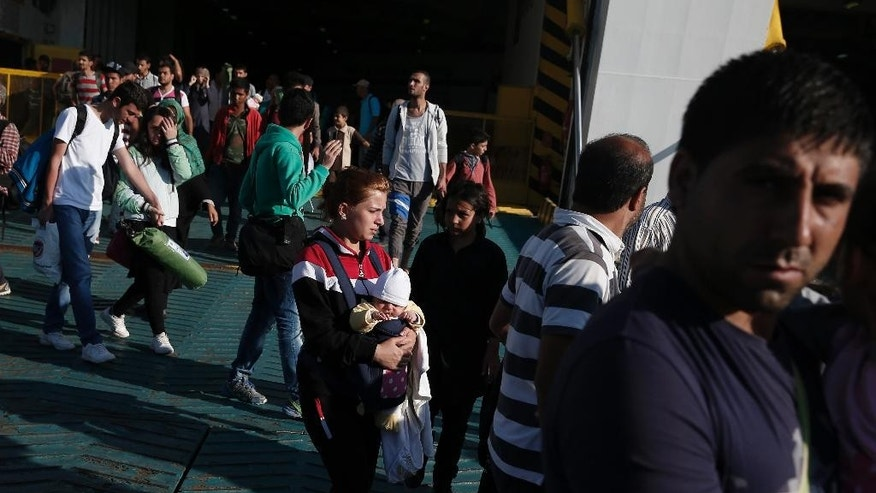 Syrian Refugees arrive on a ferry at the port of Piraeus, near Athens, Saturday, Aug. 29, 2015. About 2,500 refugees from the islands of Lesbos,  Kos and Leros , which they reached in small boats from nearby Turkey, arrived at the port .Greece has been overwhelmed this year by record numbers of migrants. (AP Photo/Petros Giannakouris)