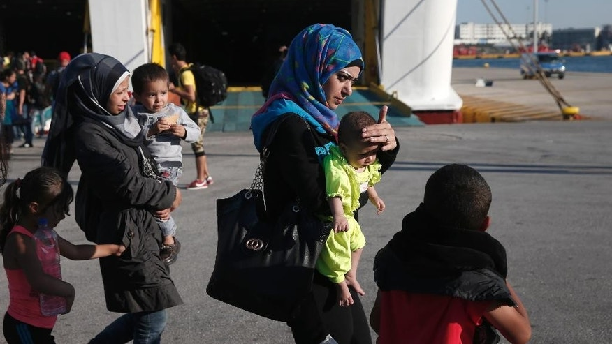 Syrian migrants disembark from a ferry at the port of Piraeus, near Athens, on Saturday, Aug. 29, 2015. About 2,500 refugees from the islands of Lesvos,  Kos and Leros, which they reached in small boats from nearby Turkey, arrive by ferry onto Greece mainland, which has been overwhelmed by migrant arrivals. (AP Photo/Petros Giannakouris)