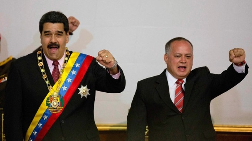 FILE - In this Monday, July 6, 2015, file photo, Venezuela's President Nicolas Maduro, left, and National Assembly President Diosdado Cabello gesture with their fists during a session at the National Assembly in Caracas, Venezuela. A crime-fighting initiative launched in July as Operation Liberate the People, has seen police kill more than 80 suspected criminals, according to an AP tally based on officialsâ statements to the media. President Maduro has not addressed the case but National Assembly President Cabello addressed the issue of human rights concerns about police killings generally in July, saying opposition groups were trying to score points by undermining what he said was an effective approach. (AP Photo/Ariana Cubillos, File)