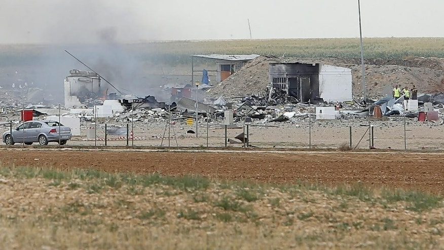 Police officers and firefighters stand by the destroyed fireworks factory Pirotecnia Zaragozana's building after a huge explosion  in Pinseque, Spain, Monday, Aug. 31, 2015. The blast at a fireworks factory in northeastern Spain killed a number of people and seriously injured tothers, police and firefighters didn't know the cause of the blast.  (AP Photo/Aranzazu Navarro)