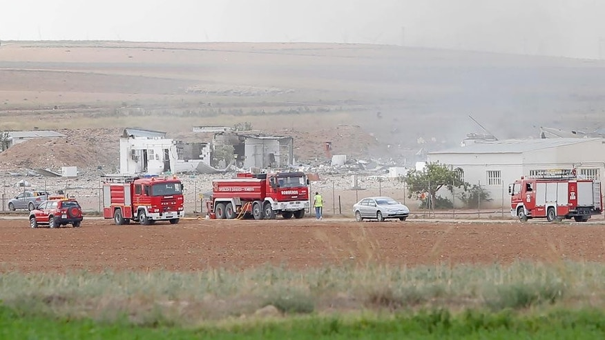 The destroyed fireworks factory Pirotecnia Zaragozana's building is seen behind firefighters trucks after a huge explosion occurred   in Pinseque, Spain, Monday, Aug. 31, 2015. The blast at a fireworks factory in northeastern Spain killed a number of people and seriously injured tothers, police and firefighters didn't know the cause of the blast. (AP Photo/Aranzazu Navarro)