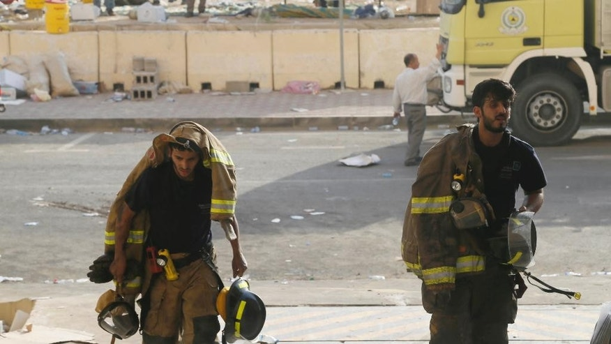 Firefighters go for a rest after putting out a fire at a multistory residential compound known as Radium that accommodates workers for state oil giant Saudi Aramco, in the eastern city of Khobar, Saudi Arabia, Sunday, Aug. 30, 2015. The fire broke out Sunday in the basement of the sprawling residential complex in Saudi Arabia's oil-rich east, killing at least 10 people and injuring more than 200, with some of the injured in critical condition, officials in the kingdom said. (AP Photo)