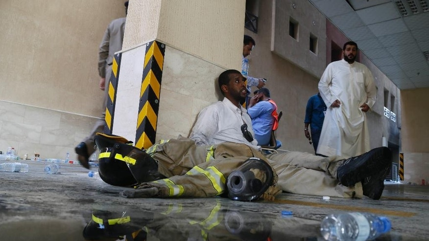Firefighters rest after putting out a fire at a multistory residential compound known as Radium that accommodates workers for state oil giant Saudi Aramco, in the eastern city of Khobar, Saudi Arabia, Sunday, Aug. 30, 2015. The fire broke out Sunday in the basement of the sprawling residential complex in Saudi Arabia's oil-rich east, killing at least 10 people and injuring more than 200, with some of the injured in critical condition, officials in the kingdom said. (AP Photo)