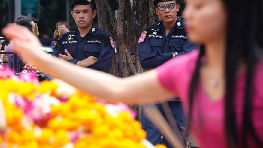 Security officers stand watch as a visitor makes an offering for Phra Phrom, the Thai interpretation of the Hindu god Brahma, at the Erawan Shrine, the scene of the Aug. 17 bombing, in Bangkok, Thailand, Monday, Aug. 31, 2015. Thai police said Monday they were seeking two new suspects - a Thai woman and a foreign man of unknown nationality - in the widening investigation into Bangkok's deadly bombing two weeks ago. (AP Photo/Charles Dharapak)