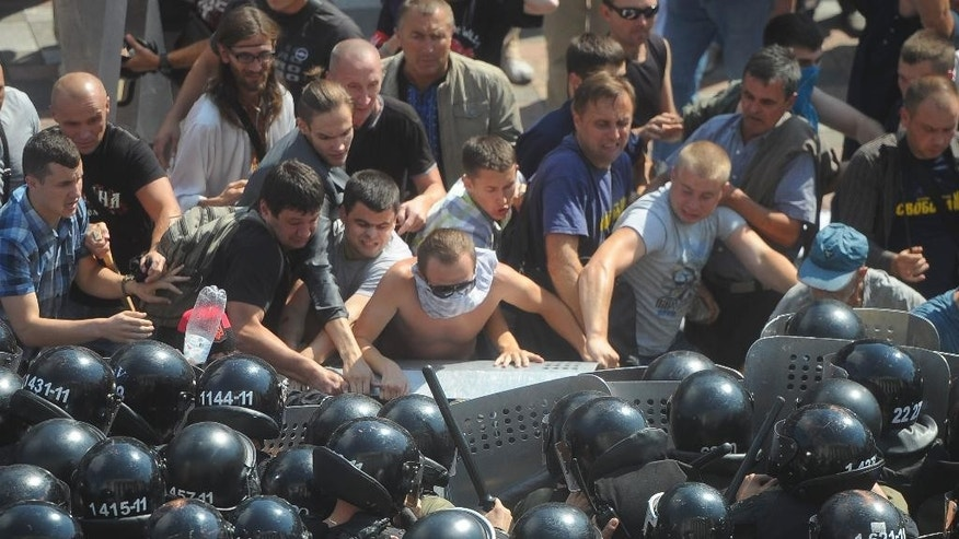 Ukrainian protesters clash with police after a vote to give greater powers to the east in front of the Parliament, Kiev, Ukraine, Monday, Aug. 31, 2015. The Ukrainian parliament has given preliminary approval to a controversial constitutional amendment that would provide greater powers to separatist regions in the east. Hundreds of people gathered in front of the parliament to protest against the amendment. (AP Photo/Andrew Kravchenko)