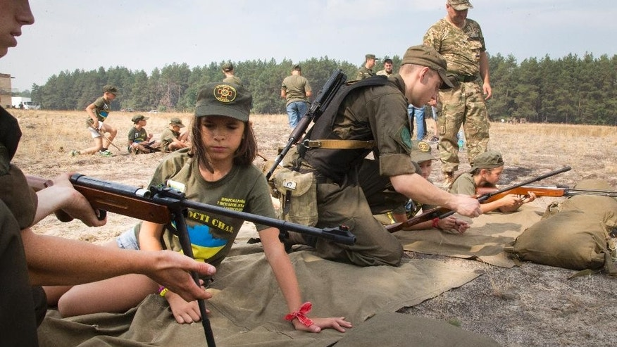 Servicemen teach children to shoot with a rifle at a military training ground of Ukraine's National Guard outside the village of Stare, the Kiev region, Ukraine, Saturday, Aug. 29, 2015. (AP Photo/Efrem Lukatsky)
