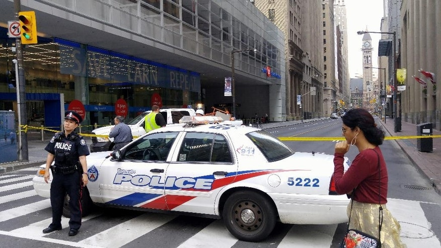 A police officer blocks an intersection at Bay Street and King Street, near the Trump International Hotel and Tower in Toronto on Monday, Aug. 31, 2015. Toronto Police closed intersections close to the Trump Tower due to an unstable antenna at the top of the building. Toronto police spokeswoman Lyn Dsey said Monday three blocks around hotel and condo tower are cordoned off. (Joe O'Connal/The Canadian Press via AP)