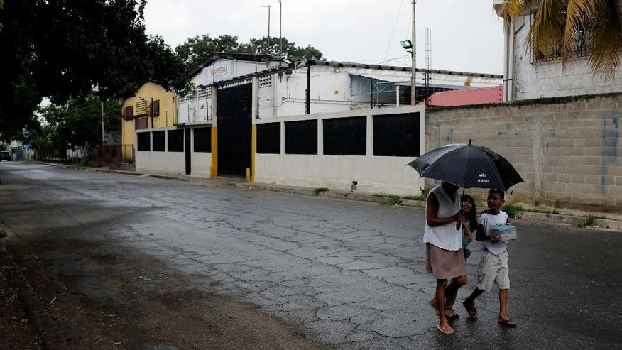 In this Thursday, Aug. 20, 2015 photo, people walk near a factory where Aragua State police officers killed four men execution-style in Maracay, Venezuela. A video secretly recorded that rainy day in early August showed that police officers took the man to a concrete alley in the complex where his three companions already lay dead, held him in place, and then shot him point blank. (AP Photo/Fernando Llano)