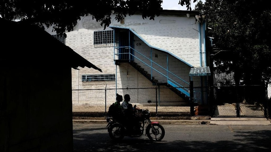 In this Thursday, Aug. 20, 2015 photo, a couple on a motorcycle rides past the main entrance of a factory where Aragua State police officers killed four men execution-style in Maracay, Venezuela. The slayings raised new concerns about a crime-fighting initiative launched this summer that aims to take back. (AP Photo/Fernando Llano)