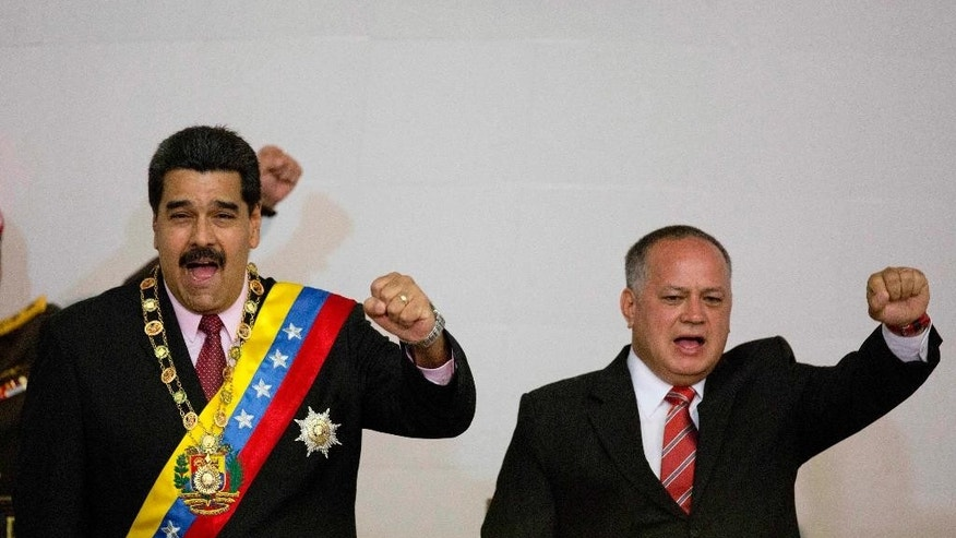 FILE - In this Monday, July 6, 2015, file photo, Venezuela's President Nicolas Maduro, left, and National Assembly President Diosdado Cabello gesture with their fists during a session at the National Assembly in Caracas, Venezuela. A crime-fighting initiative launched in July as Operation Liberate the People, has seen police kill more than 80 suspected criminals, according to an AP tally based on officials' statements to the media. President Maduro has not addressed the case but National Assembly President Cabello addressed the issue of human rights concerns about police killings generally in July, saying opposition groups were trying to score points by undermining what he said was an effective approach. (AP Photo/Ariana Cubillos, File)