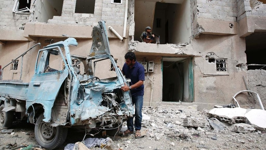 A Yemeni man inspects a vehicle destroyed by a Saudi air strike in Sanaa, Yemen, Monday, Aug. 31, 2015. (AP Photo/Hani Mohammed)