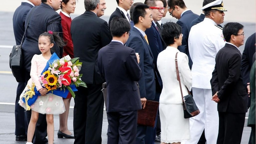 A girl stands with a bouquet of flowers as people wait for Venezuela's President Nicolas Maduro to arrive at Beijing Capital International Airport in Beijing, China, Tuesday, Sept. 1, 2015. Russian leader Vladimir Putin, South Korean President Park Geun-hye and U.N. Secretary General Ban Ki-moon shine at the top of China's guest list at this week's grand commemorations of the 70th anniversary of Japan's defeat in World War II, but high-level representatives from Western democracies are largely absent. (AP Photo/Ng Han Guan)