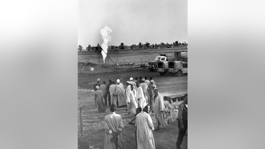 """FILE - In this Nov. 25, 1966 file photo, farmers look at a towering flame at an outburst of natural gas, discovered by the Italian oil company ENI in the Nile Delta region of Kafr el-Sheikh, Egypt. Italian energy company Eni SpA said Sunday, Aug. 30, 2015, that it found the """"largest-ever"""" gas field in the Mediterranean Sea off Egypt's shores. Egypt's new natural gas bonanza is causing an uproar in Israel, with energy stocks plummeting and recriminations over dithering and infighting that has delayed production from the country's own gas fields. (AP Photo/Aly Mahmoud)"""