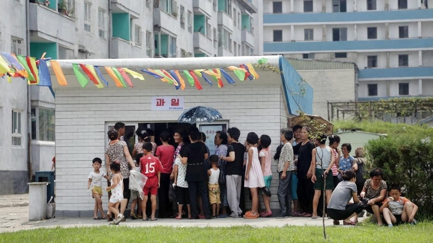 In this Aug. 16, 2015 photo, people queue up at kiosk in Pyongyang, North Korea. Street stalls that offer North Koreans a place to spend - or make - money on everything from snow cones to DVDs are flourishing in Pyongyang and other North Korean cities, modest but growing forms of private commerce in a country where capitalism is officially anathema. (AP Photo/Dita Alangkara)
