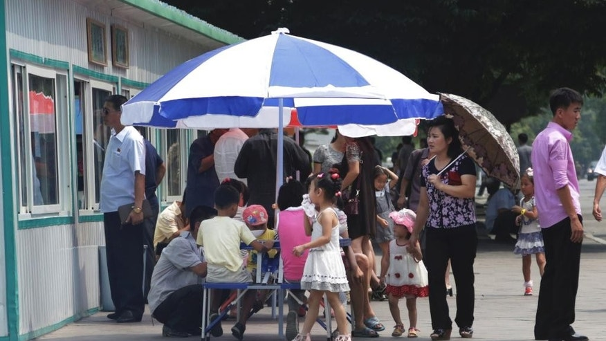 In this Aug. 16, 2015 photo, people queue up and have their meals at a food kiosk in Pyongyang, North Korea. Street stalls that offer North Koreans a place to spend - or make - money on everything from snow cones to DVDs are flourishing in Pyongyang and other North Korean cities, modest but growing forms of private commerce in a country where capitalism is officially anathema. (AP Photo/Dita Alangkara)