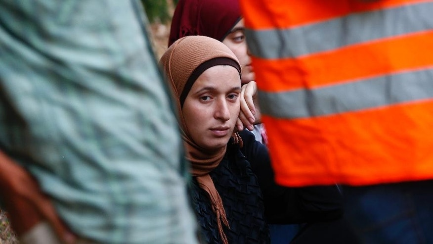 A young Syrian woman sits besides a road after making her way from Austria to Germany at the highway A3 in Pocking near Passau, Germany,  Tuesday, Sept. 1, 2015. Hundreds of migrants are arriving every day, after making perilous journeys through Europe. (AP Photo/Matthias Schrader)