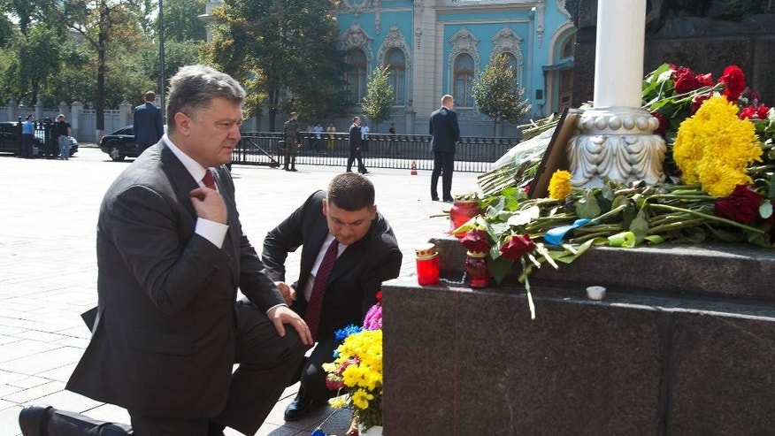 Ukraine's President Petro Poroshenko, left, and parliament speaker Volodymyr Groisman lay flowers by the photo of a police officer who was killed in a Monday clash, in front of Parliament in Kiev, Ukraine, Tuesday, Sept. 1, 2015. Ukrainian police say 141 people remain hospitalized after a nationalist protest in Kiev turned violent, with 10 of the injured in serious condition. Two officers died from their wounds. (Anastasiia Sirotkina, Pool photo via AP)