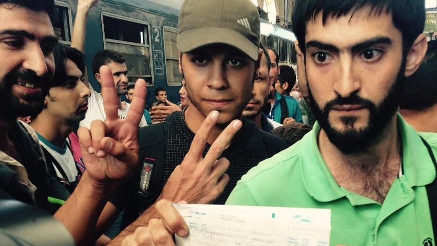 Syrian migrants show their train tickets to Germany and demand being let on the train but Keleti train terminal in Budapest, Hungary, was closed Tuesday morning Sept. 1, 2015 for an indefinite time. (AP Photo/Pablo Gorondi)