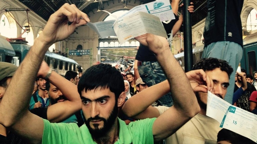 Syrian migrants show their train tickets to Germany and demand being let on the train but Keleti train terminal in Budapest, Hungary, was closed Tuesdsy morning Sept. 1, 2015 for an indefinite time. (AP Photo/Pablo Gorondi)