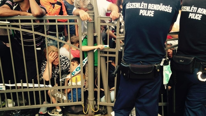 Migrants wait behind a fence guarded by police as the Keleti train terminal in Budapest, Hungary, was closed Tuesday morning Sept. 1, 2015 for an indefinite time. (AP Photo/Pablo Gorondi)