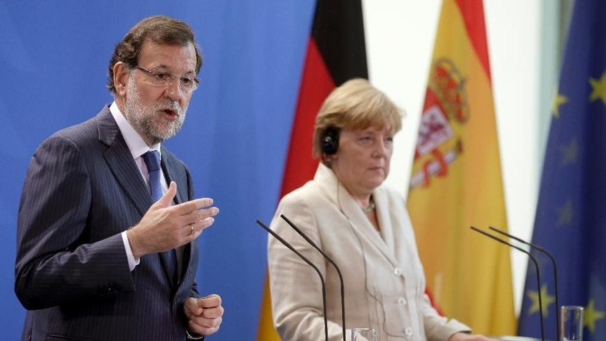 German Chancellor Angela Merkel, right, and the Prime Minister of Spain, Mariano Rajoy, address the media during a joint press conference as part of a meeting in Berlin, Germany, Tuesday, Sept. 1, 2015. (AP Photo/Michael Sohn
