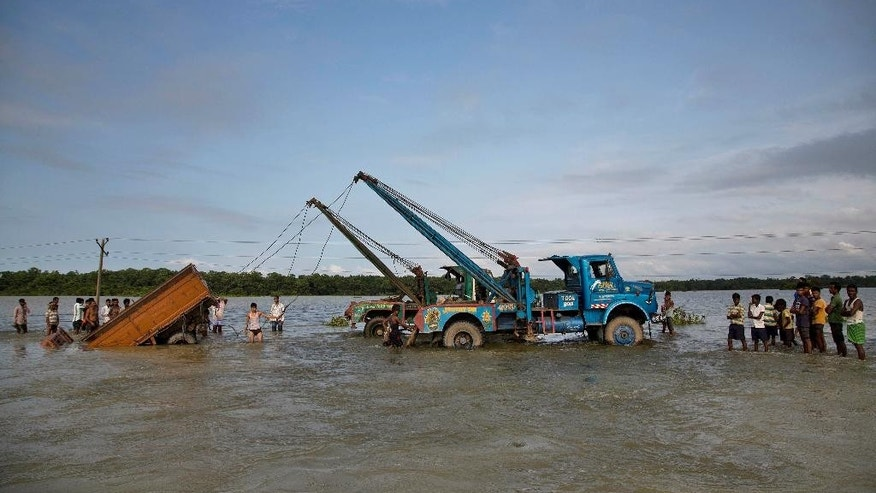 Tow trucks pull a vehicle that was swept off after it tried to cross a flooded road at Pobitora village, about 55 kilometers (34 miles) east of Gauhati, India, Tuesday, Sept. 1, 2015. Monsoon floods have inundated hundreds of villages across the northeast Indian state of Assam, killing several people and forcing some 800,000 people to leave their homes. (AP Photo/Anupam Nath)