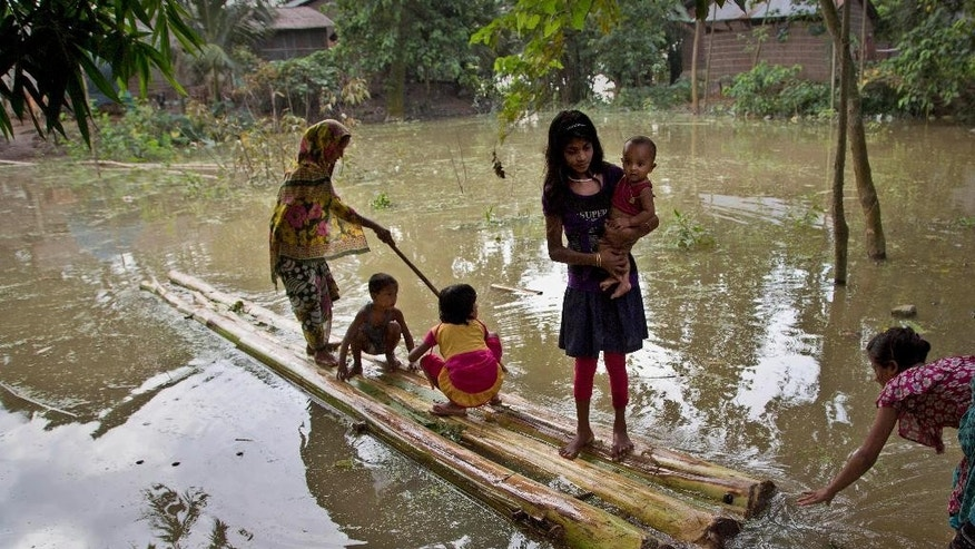 An Indian family prepare to cross floodwaters on a banana raft at Balimukh village, about 70 kilometers (43 miles) east of Gauhati, India, Tuesday, Sept. 1, 2015. Monsoon floods have inundated hundreds of villages across the northeast Indian state of Assam, killing several people and forcing some 800,000 people to leave their homes. (AP Photo/Anupam Nath)